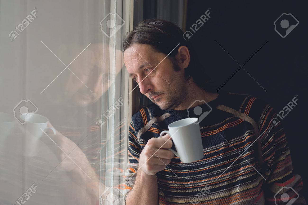 Sad alone mid adult man standing by the window and drinking coffee, looking somewhere in the distance. - 34130508