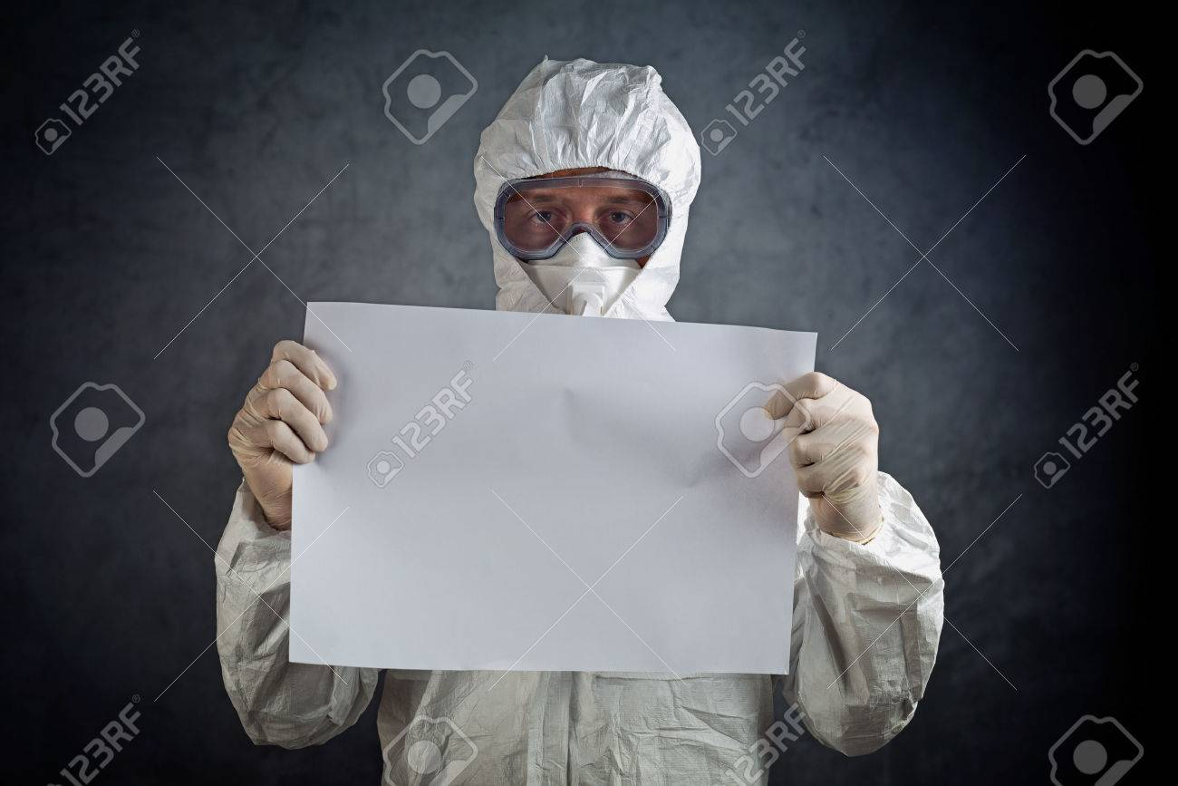 Medical healh care worker wearing protective gown, gloves, mask and goggles and holding blank paper as copy space. - 34130533