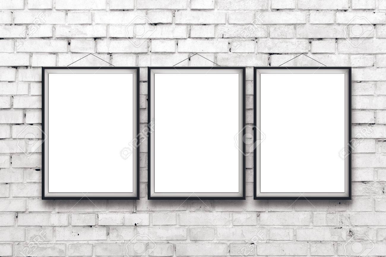 stock photo three blank vertical painting poster in black frame hanging on white brick wall painting proportions match international paper size a