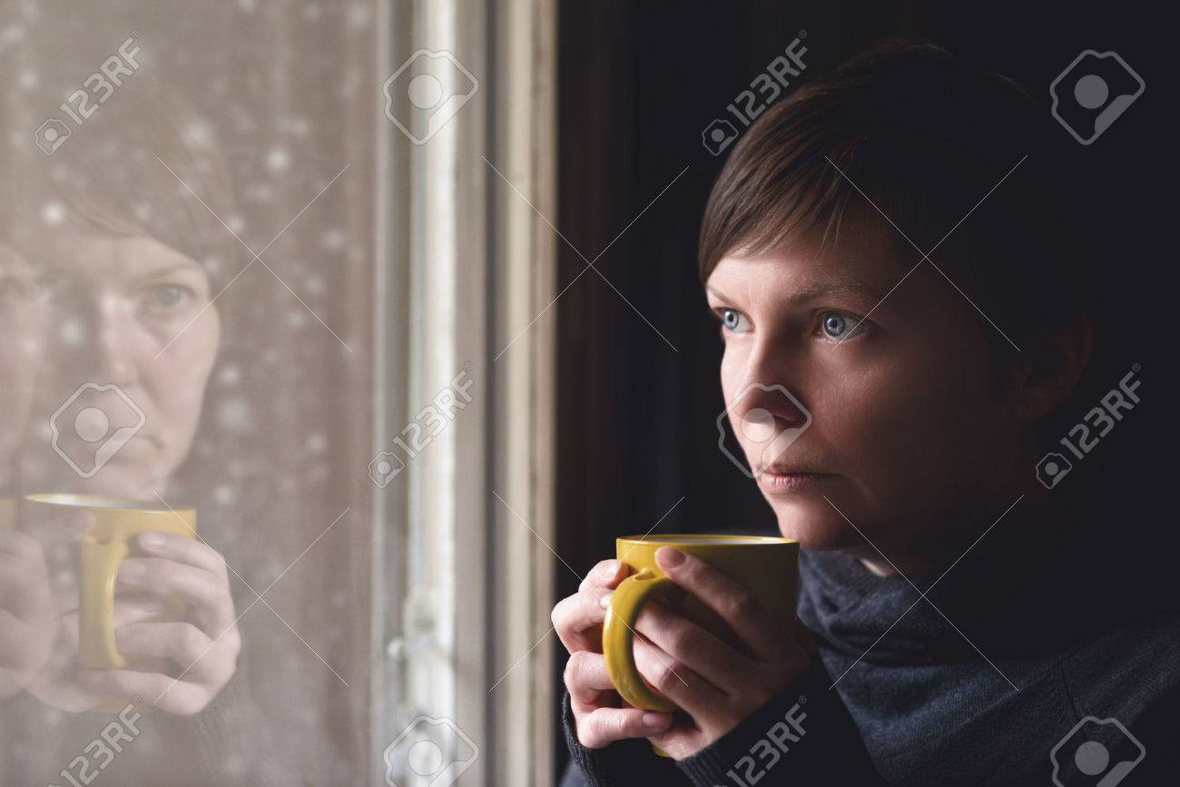 Lonelsome woman drinking cup of coffee by the window of her living room, looking out at snow falling with a sad look on her face. Selective focus with shallow depth of field. - 34315102