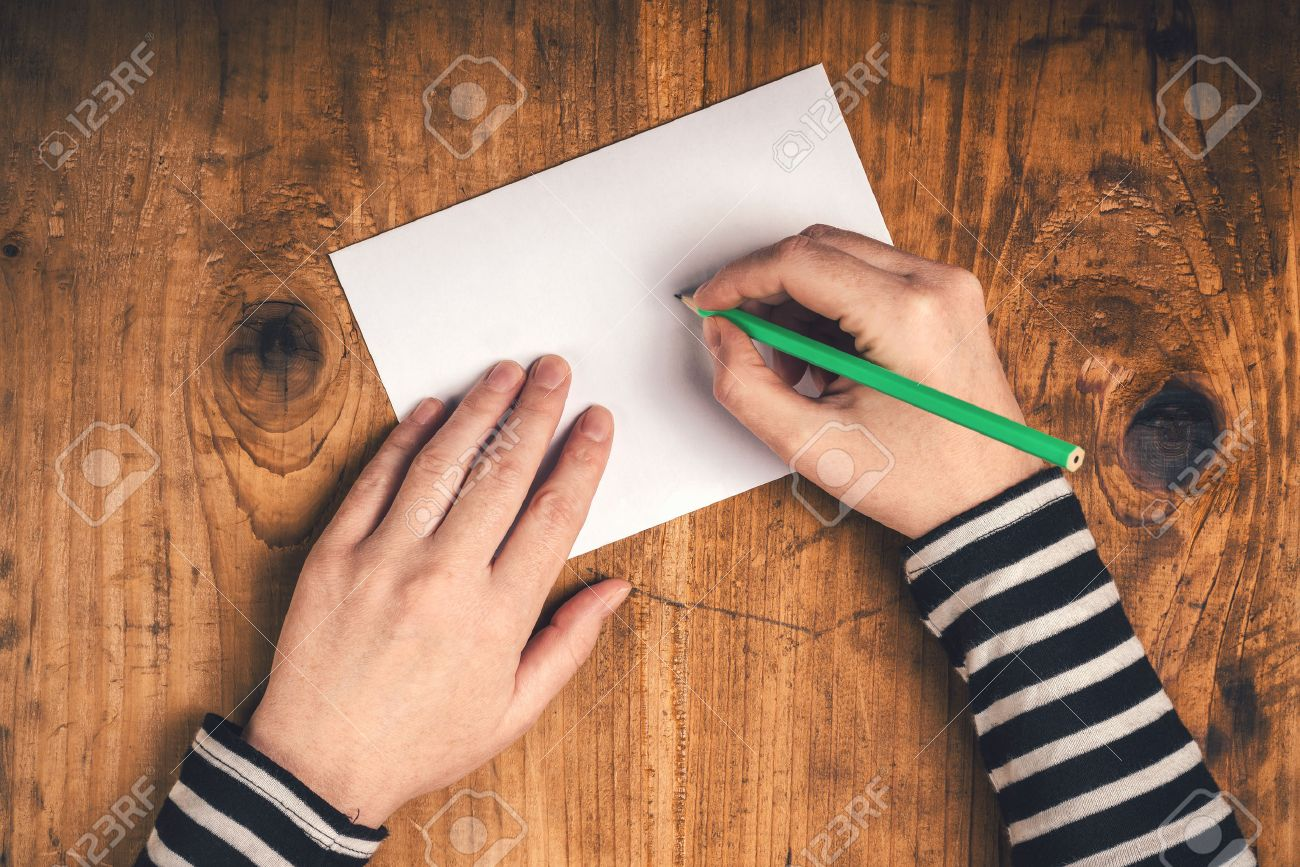 stock photo woman writing recipient address on mailing envelope female hands from above on office desk sending letter top view retro toned