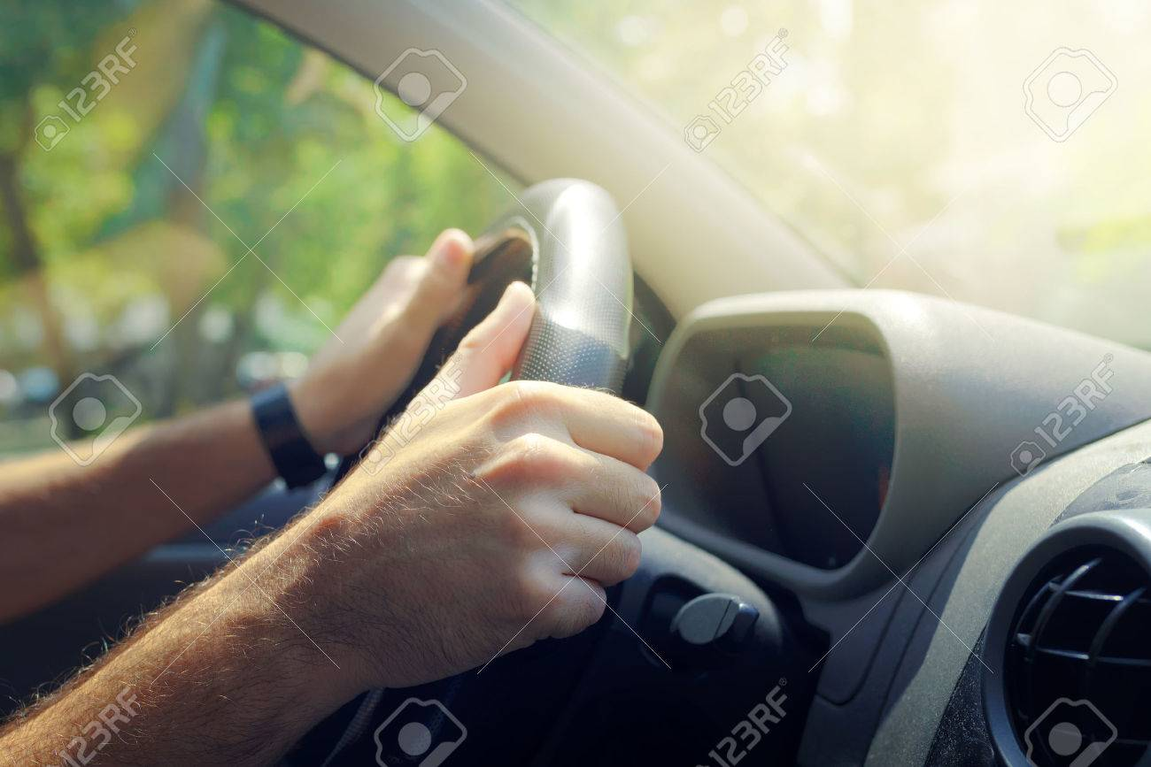 Male hands holding car steering wheel the right way for safe driving - 62392410