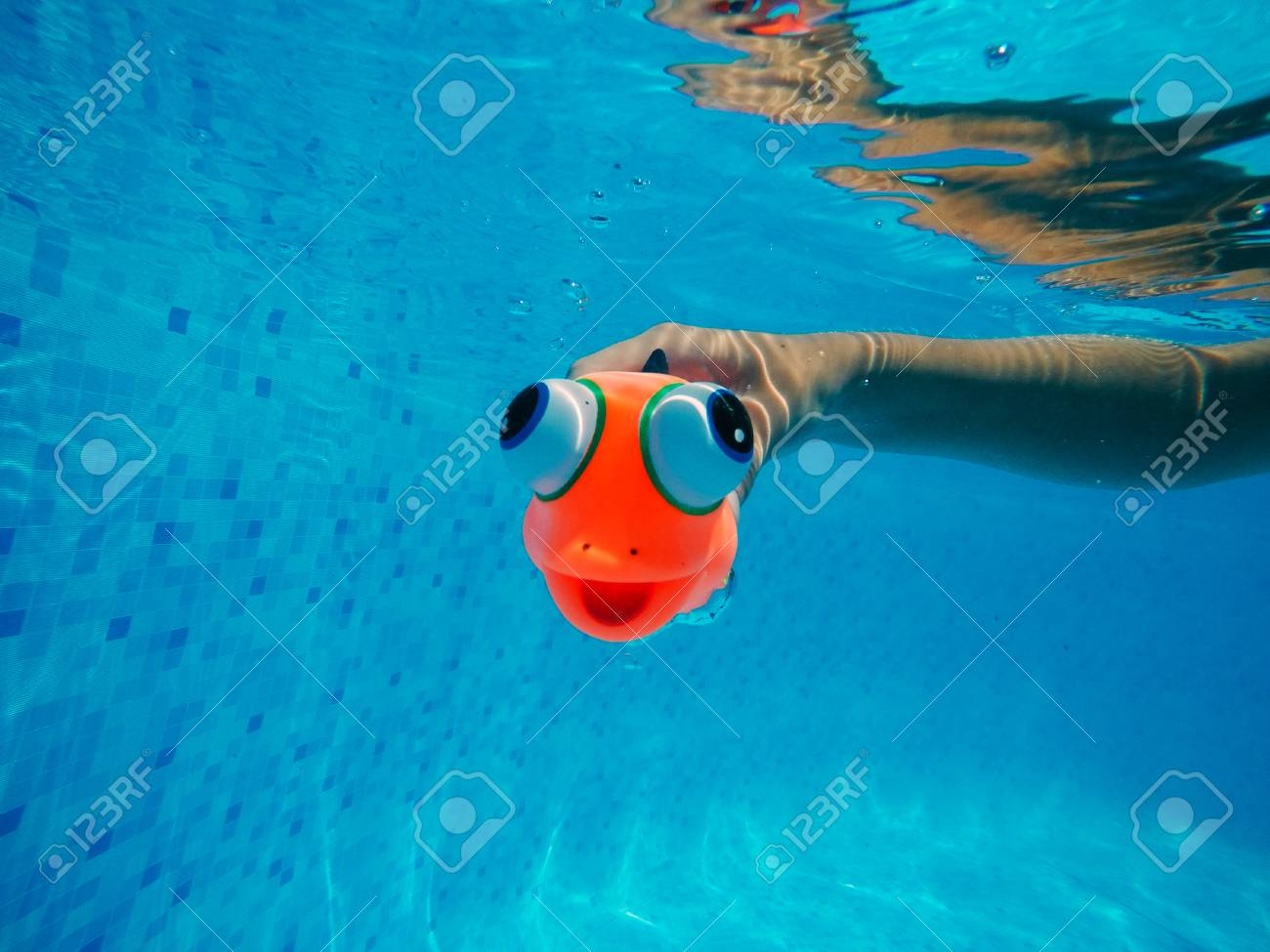 Child playing with generic rubber fish toy in swimming pool,..