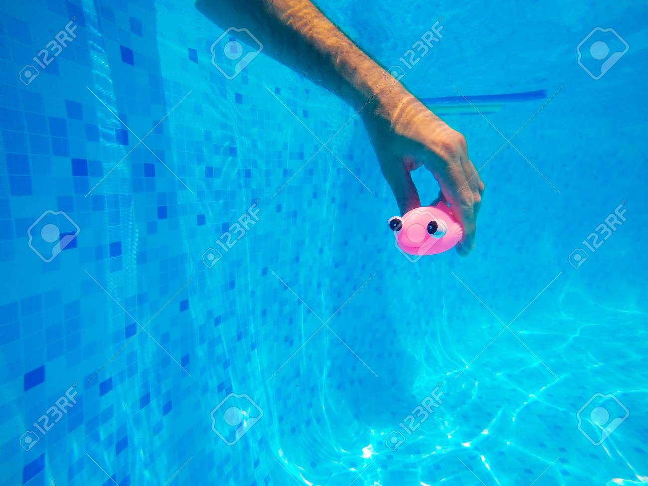Man playing with generic rubber fish toy in swimming pool, summertime..
