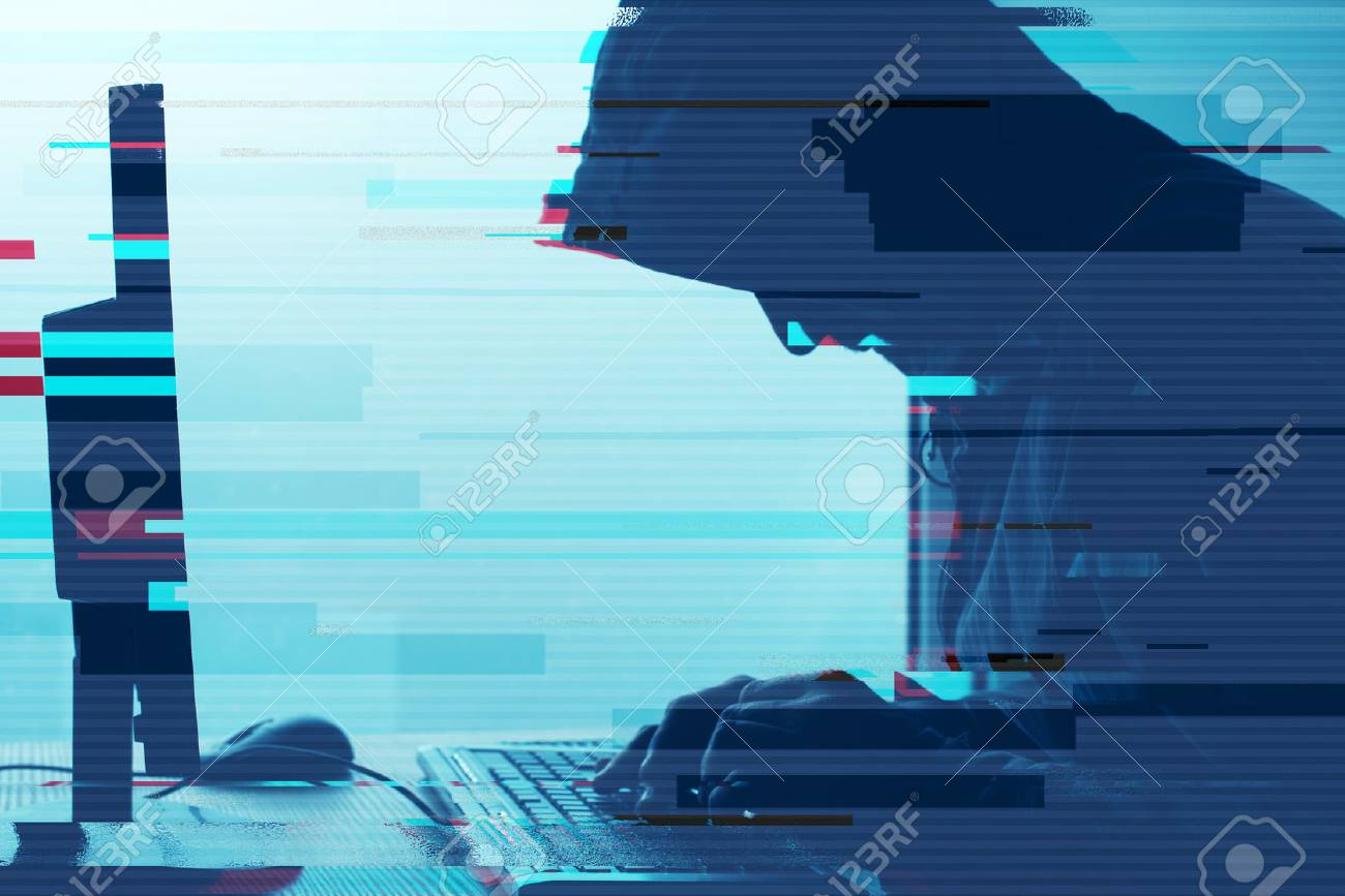 Hooded computer hacker working on desktop PC computer. P2P and piracy, computer virus and trojans, phishing, malware and ransomware concept with glitch effect. - 87910784