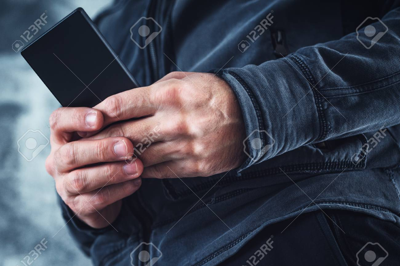 Low angle view of casual adult man reading private SMS text message on his  personal mobile