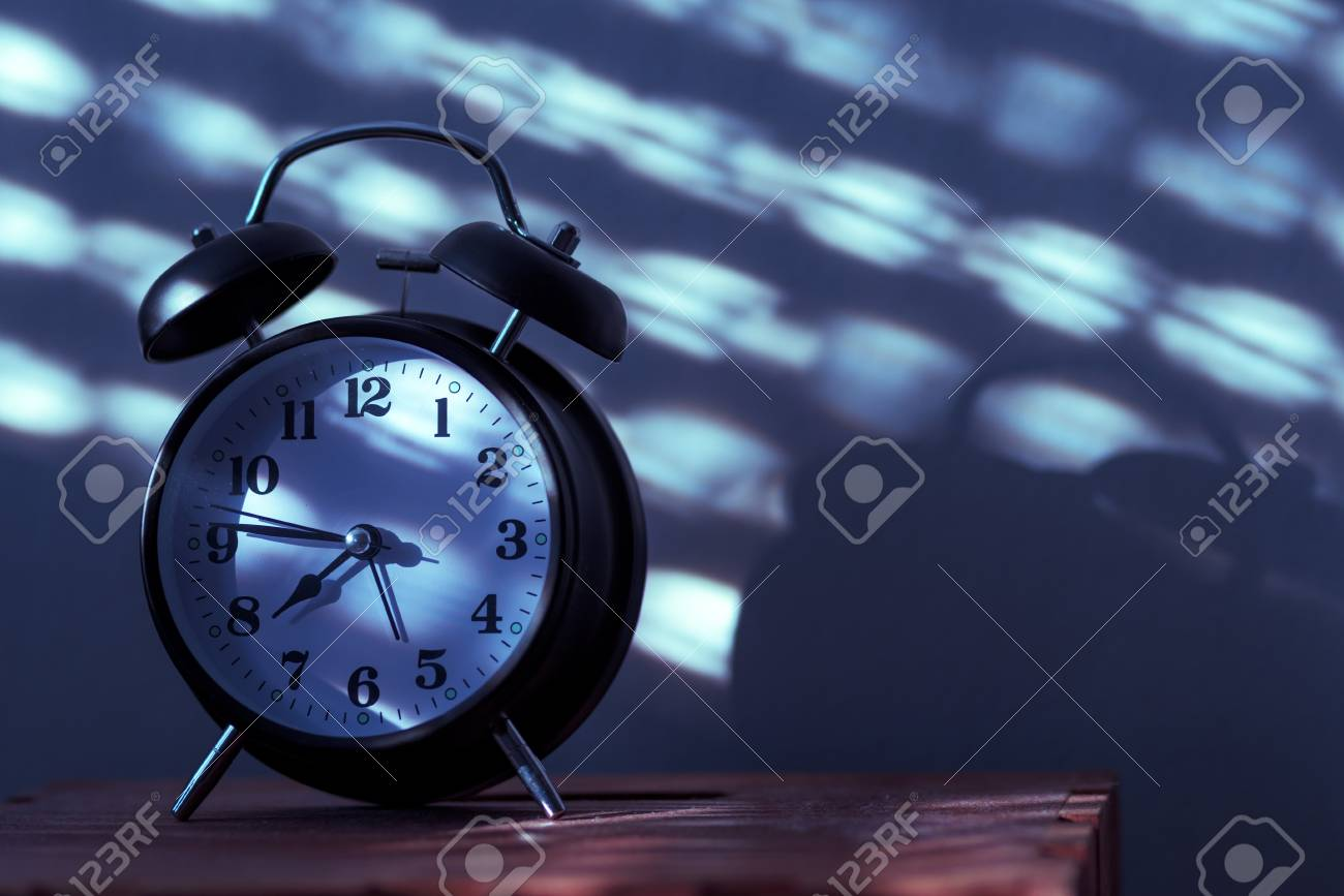 Alarm Clock On Night Table In Bedroom Ticking Time In Early Morning With  Sunlight And Shadows