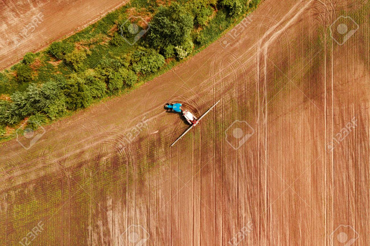 Tractor spraying crops in field, aerial view from drone pov
