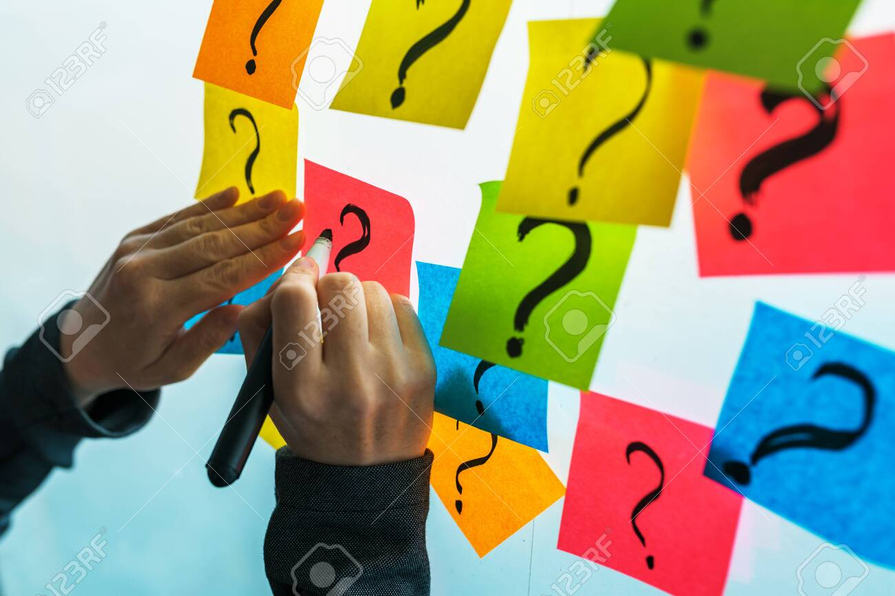 Businesswoman writing question marks on colorful sticky note paper on office whiteboard, selective focus - 123224278