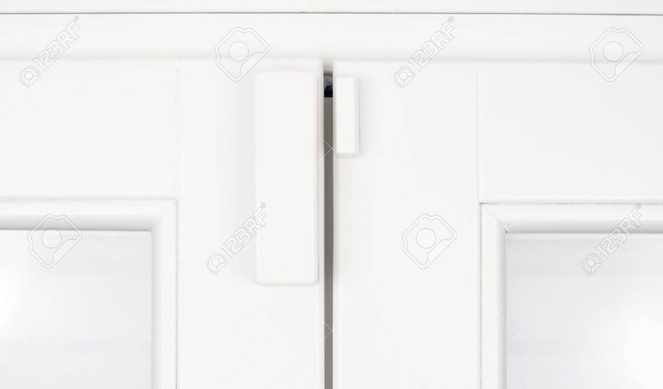 Wireless battery magnetic alarm sensor for window and door on white wooden sash detail Stock Photo - 13761958