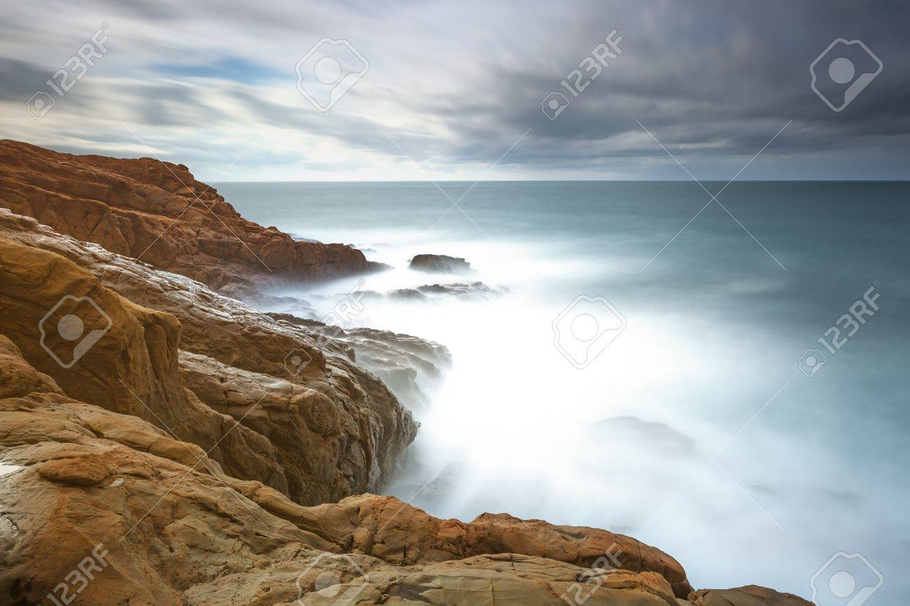 Dark red rocks, waves and foam, ocean under cloudy sky in a bad weather  Long exposure photography  Livorno, Tuscany, Italy Stock Photo - 17195648