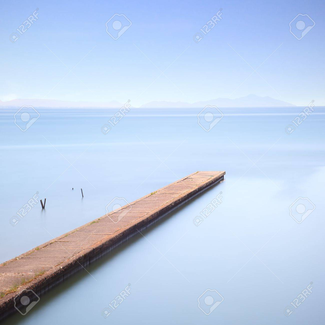 Concrete pier or jetty on a blue sea  Hills on background  Long exposure photography in Lido Camaiore, Versilia, Tuscany, Italy, Europe Stock Photo - 17811063