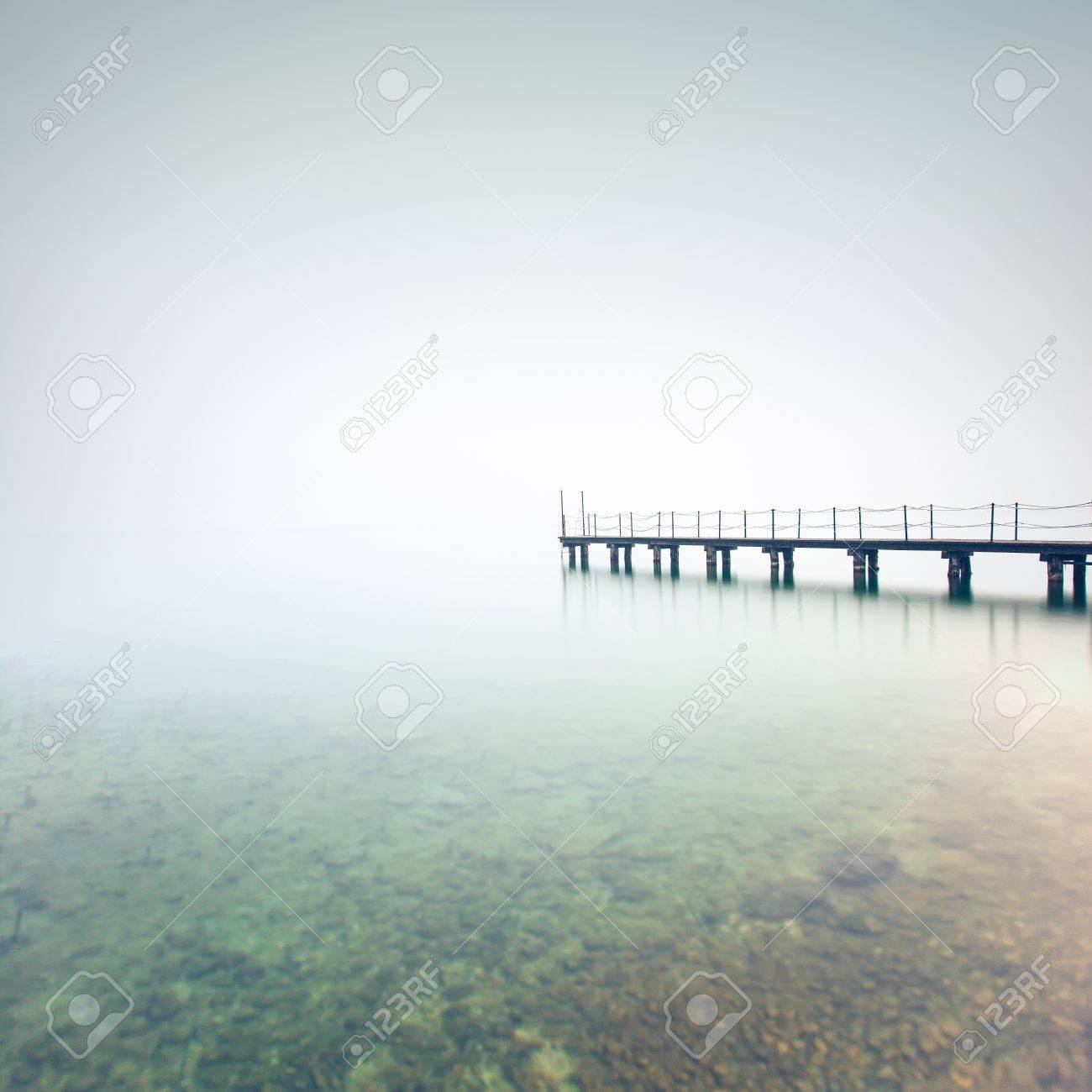 Pier or jetty silhouette in a foggy lake  Garda lake, Italy, Europe Stock Photo - 18590249