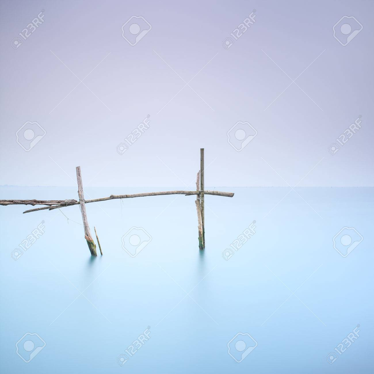 Fishing poles for clams and mussels and soft water on a quiet foggy landscape  Long exposure photography Stock Photo - 27911538