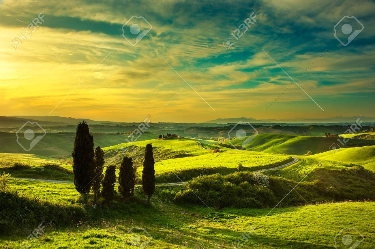 Tuscany, rural sunset landscape. Countryside farm, cypress trees, green field, sun light and cloud. Volterra, Italy, Europe. - 45989338