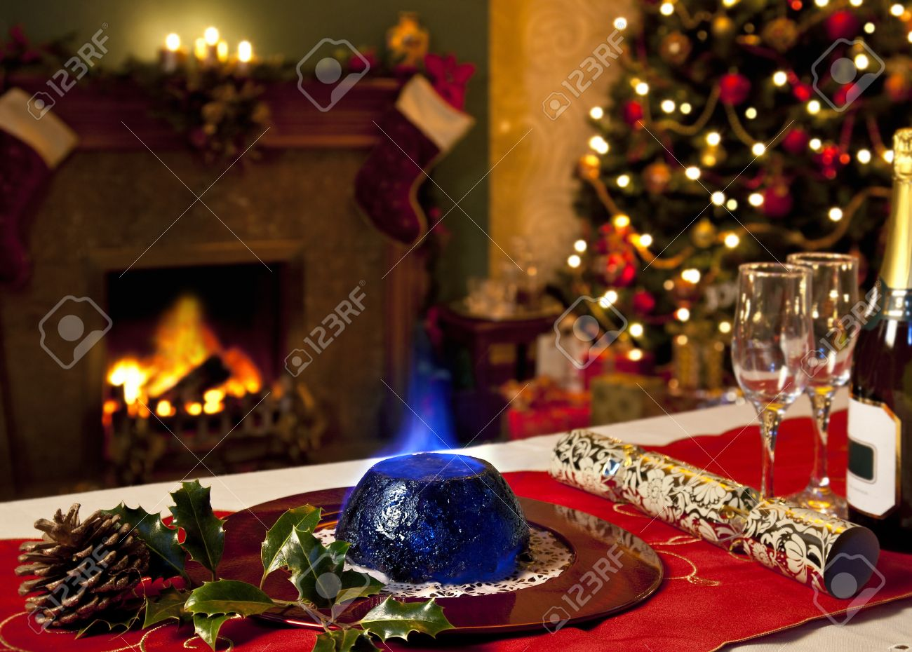 a christmas pudding with burning brandy topping with a festive