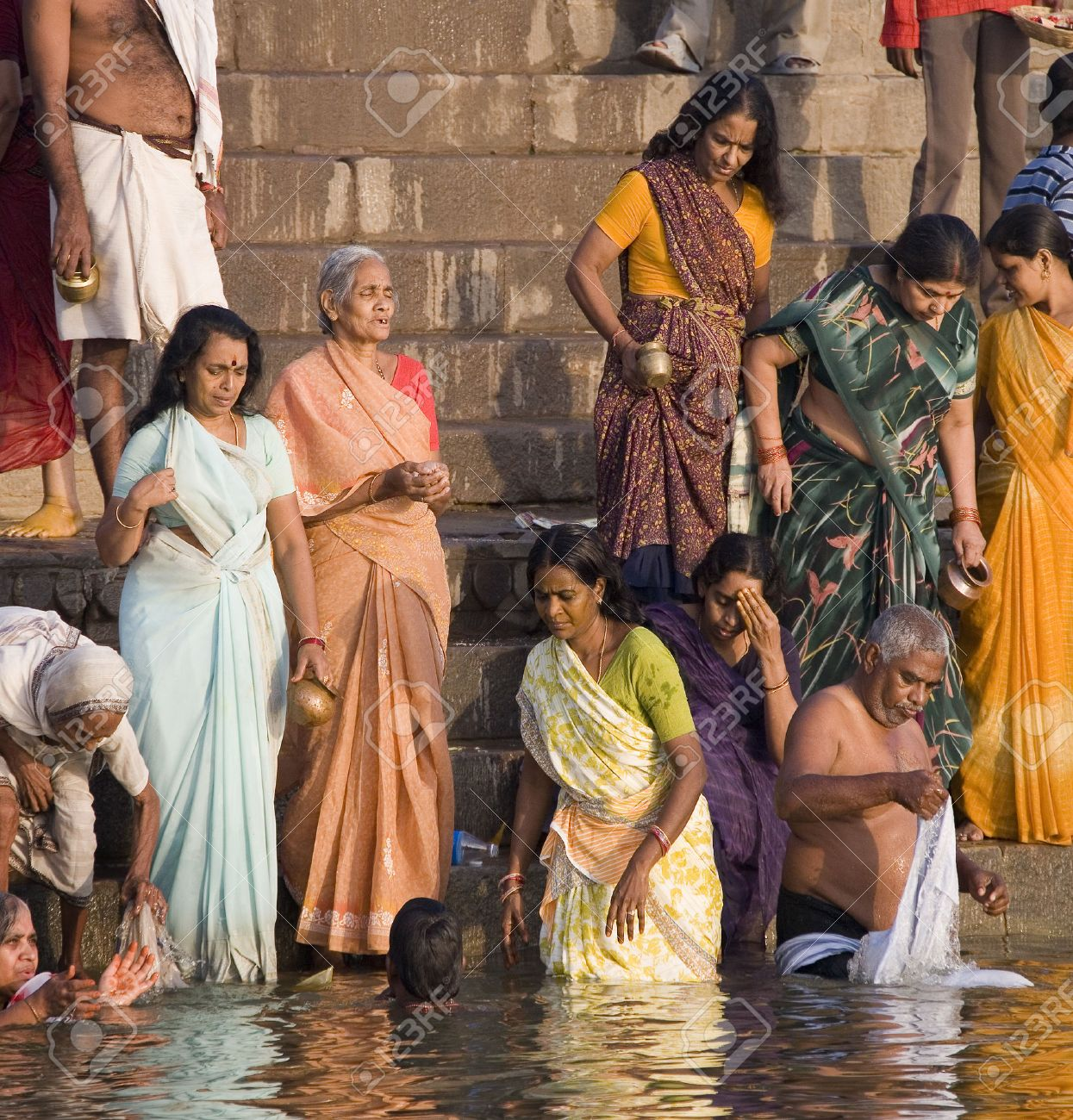 Group of pilgrims on the Hindu ghats on the banks of the Holy River Ganges (Ganga) in Varanasi (Benares) in the Uttar Pradesh region of northern India. - 22358553