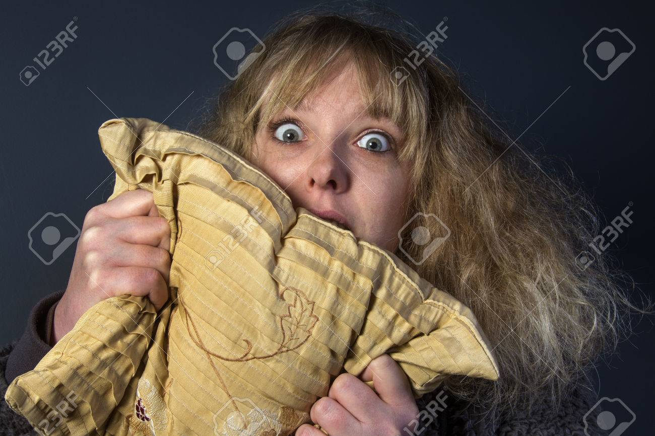 A frightened young woman watching a horror movie - 26166434