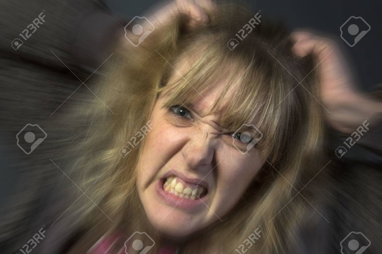 A very angry young woman tearing her hair out - 26166439