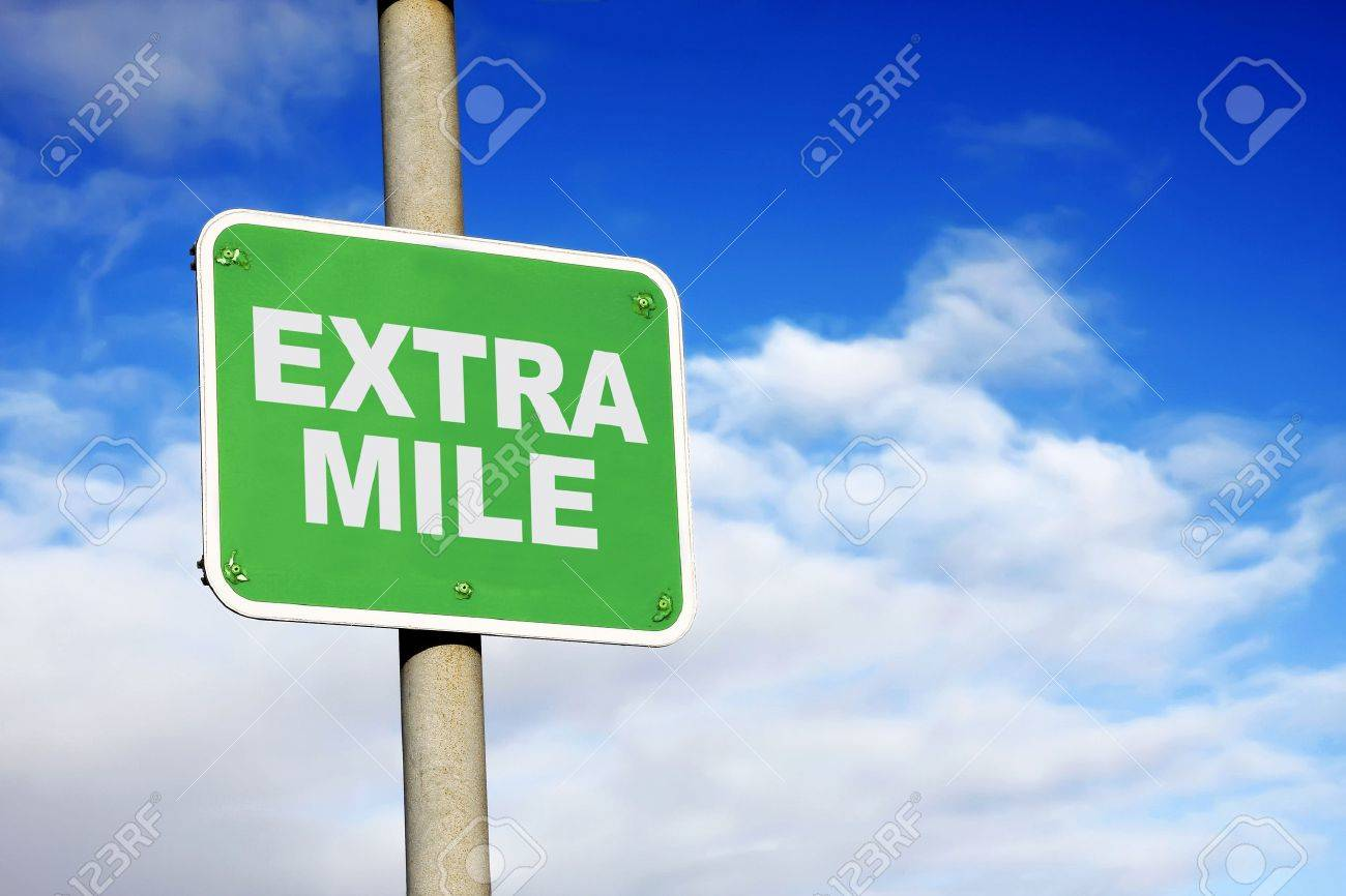 Green extra mile sign against a blue sky - 14273010