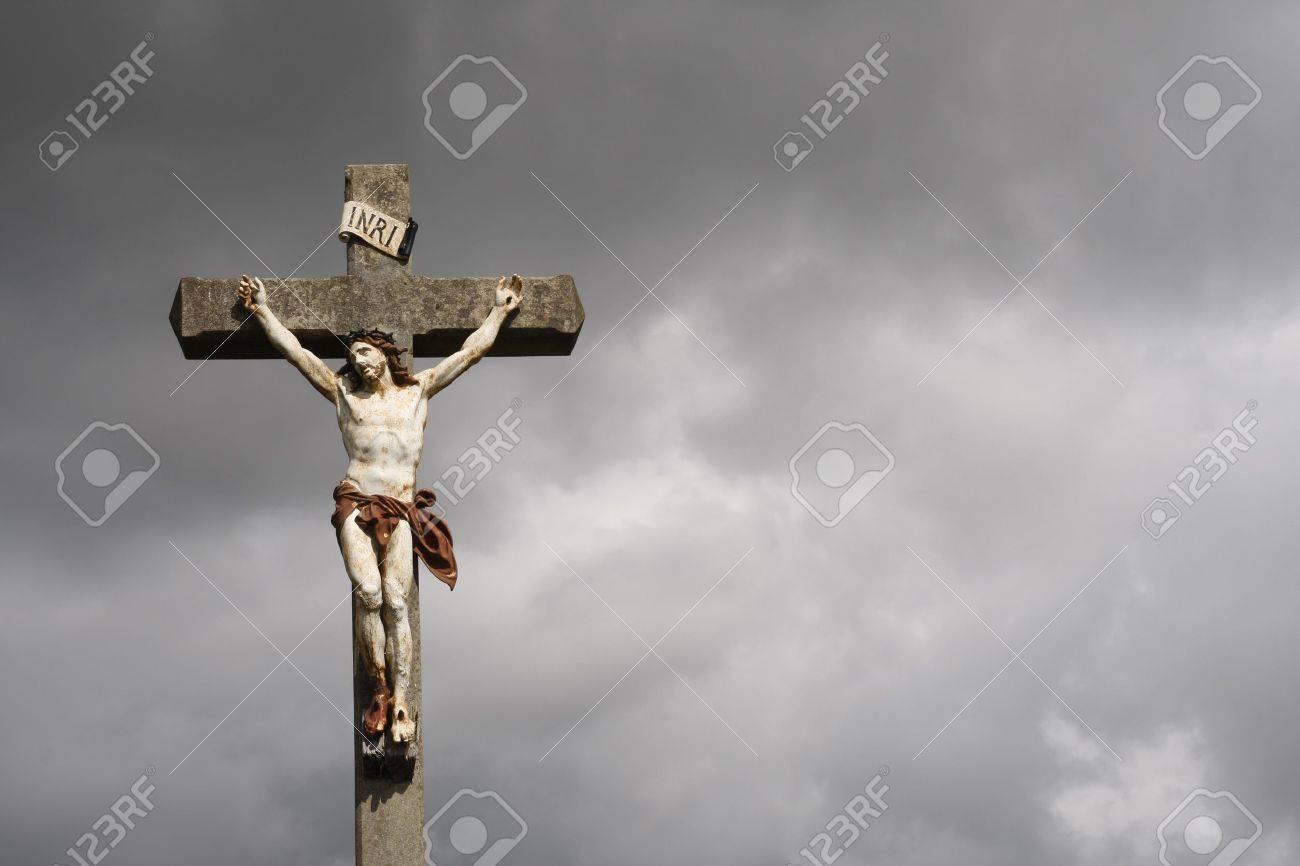 Jesus Christ crucifixion sculpture against dark clouds - 15069665