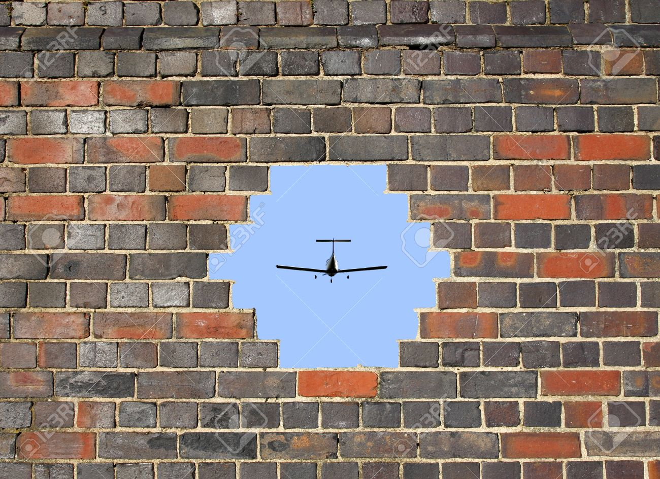 Small plane through a hole in a brick wall background - 16239578