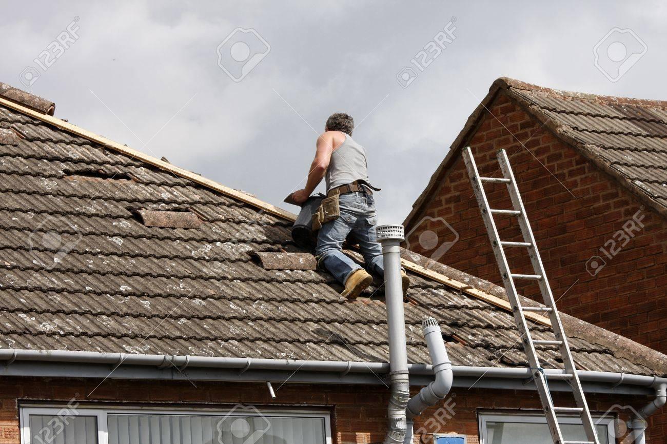 Workman repairing the ridge tiles on a roof - 17802446