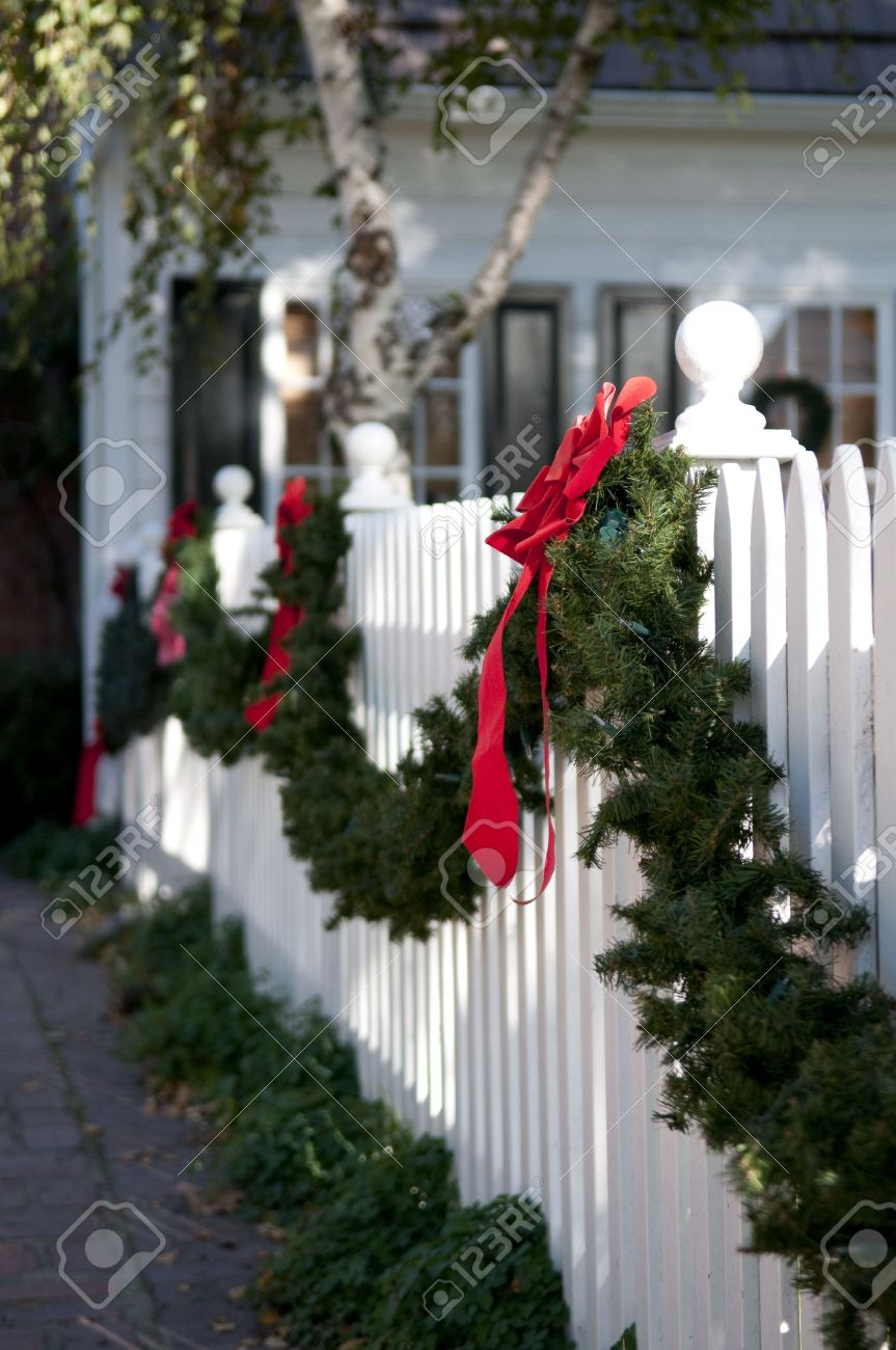 garland with red bows hanging on white picket fence Stock Photo - 6030848