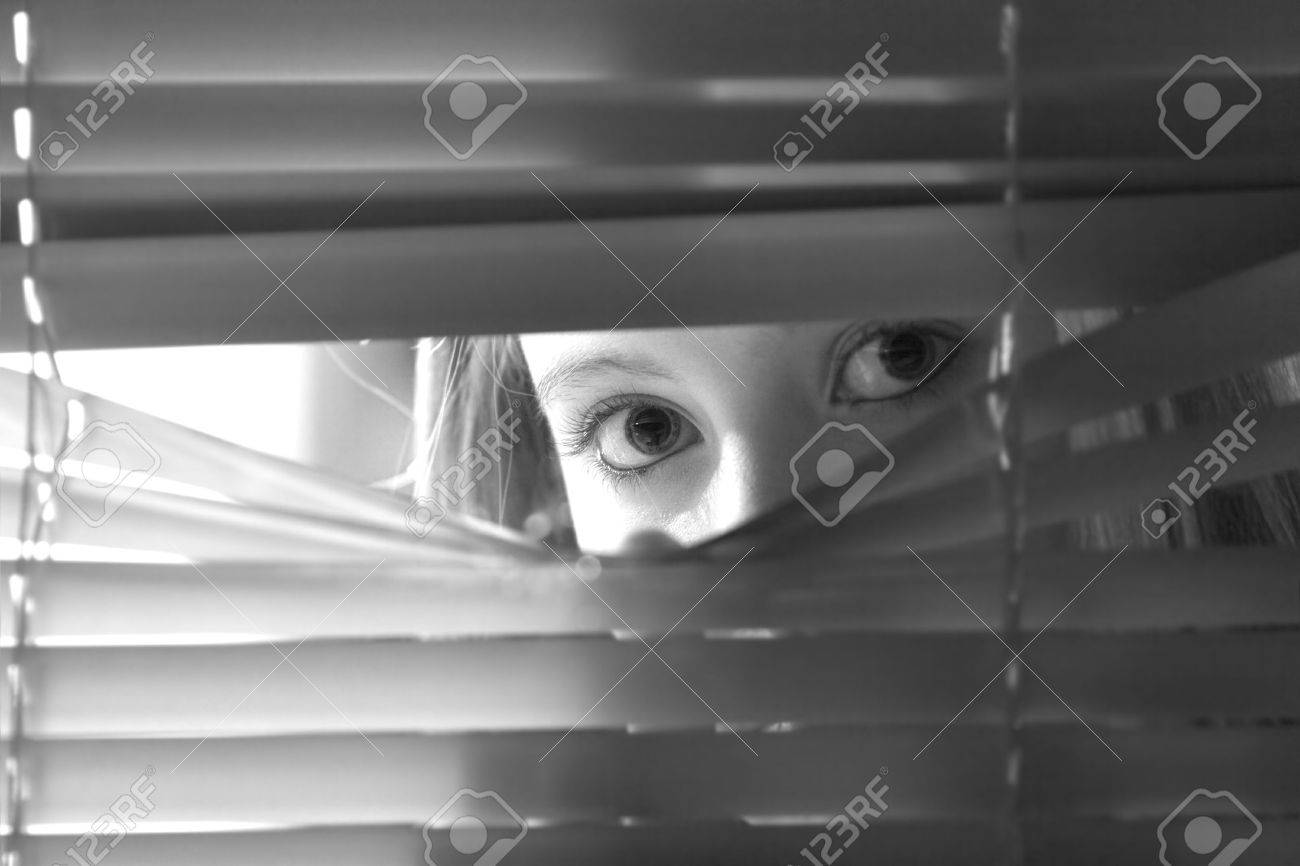 Young female looking through window blinds at night.(shallow depth of field) Stock Photo - 725547