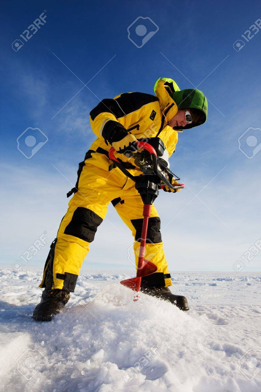 Ice fisherman drilling a hole on a frozen lake with a power auger Stock Photo - 4145791