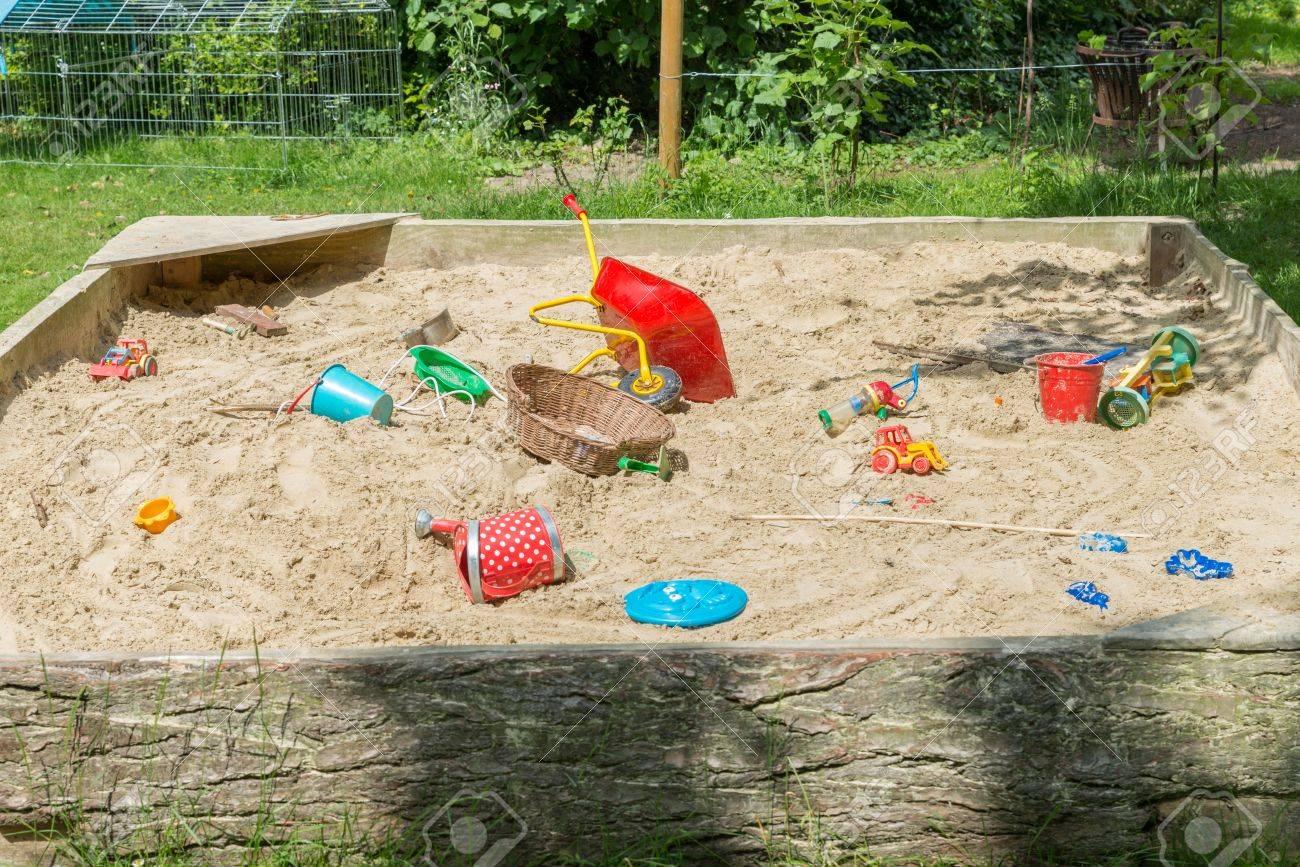 großer sandkasten mit vielen spielsachen im garten lizenzfreie fotos