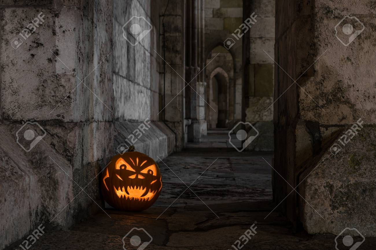 halloween pumpkin in front of ancient stone wall of a church germany stock photo