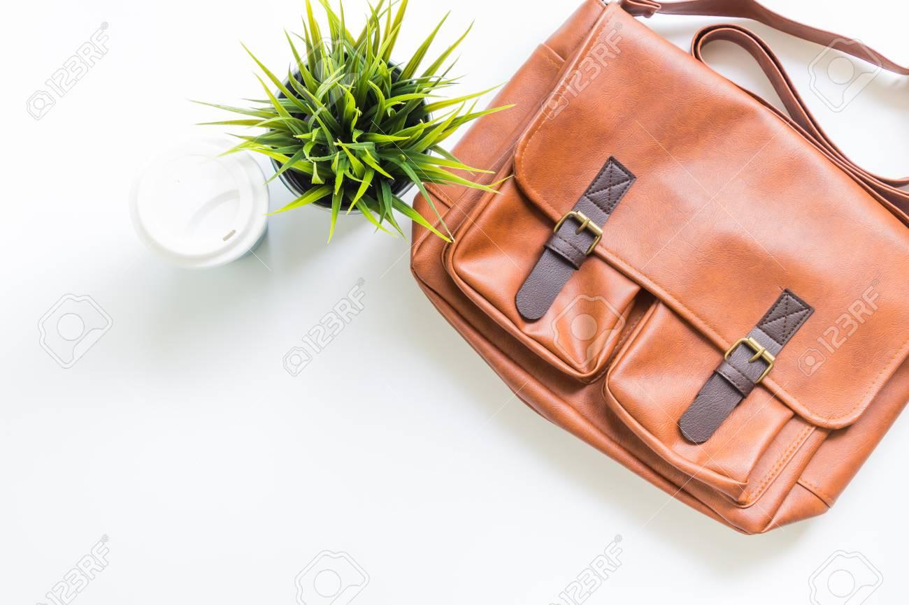 Accesorios para hombres con bolsos de cuero marrón, decoración de árbol y taza de café caliente, plano, vista desde arriba.