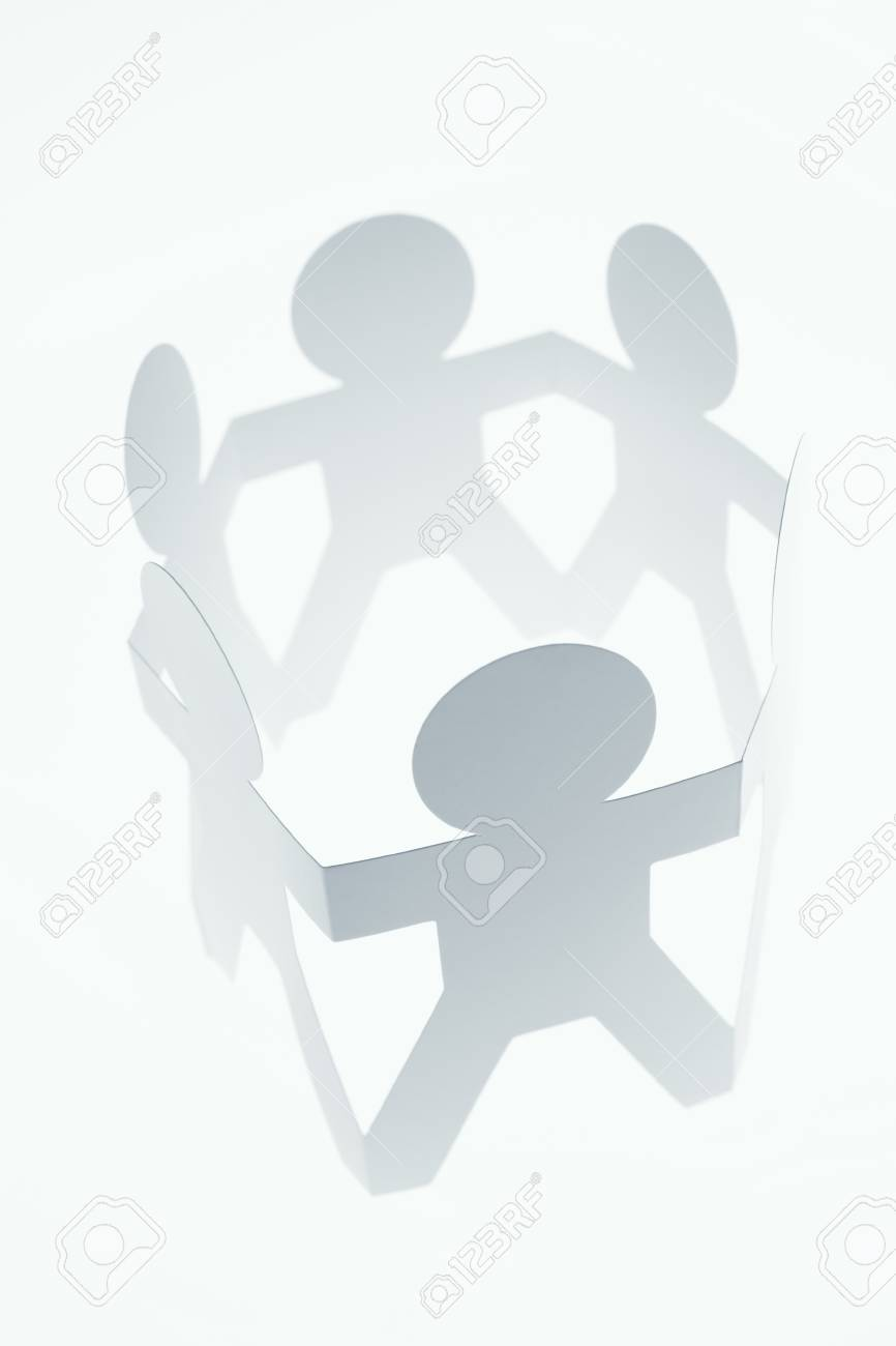 Group of paper chain people holding hands together. Stock Photo - 17455306