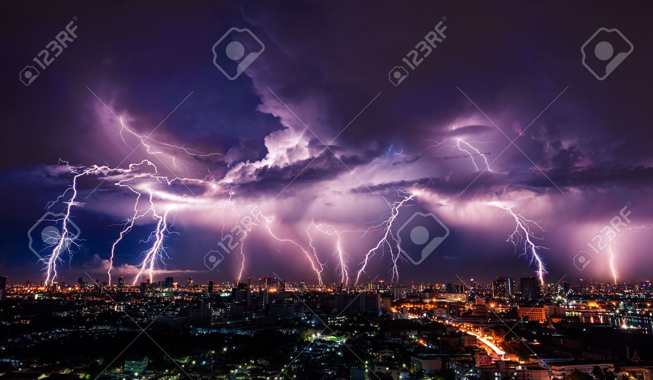 Lightning Storm Over City In Purple Light Stock Photo