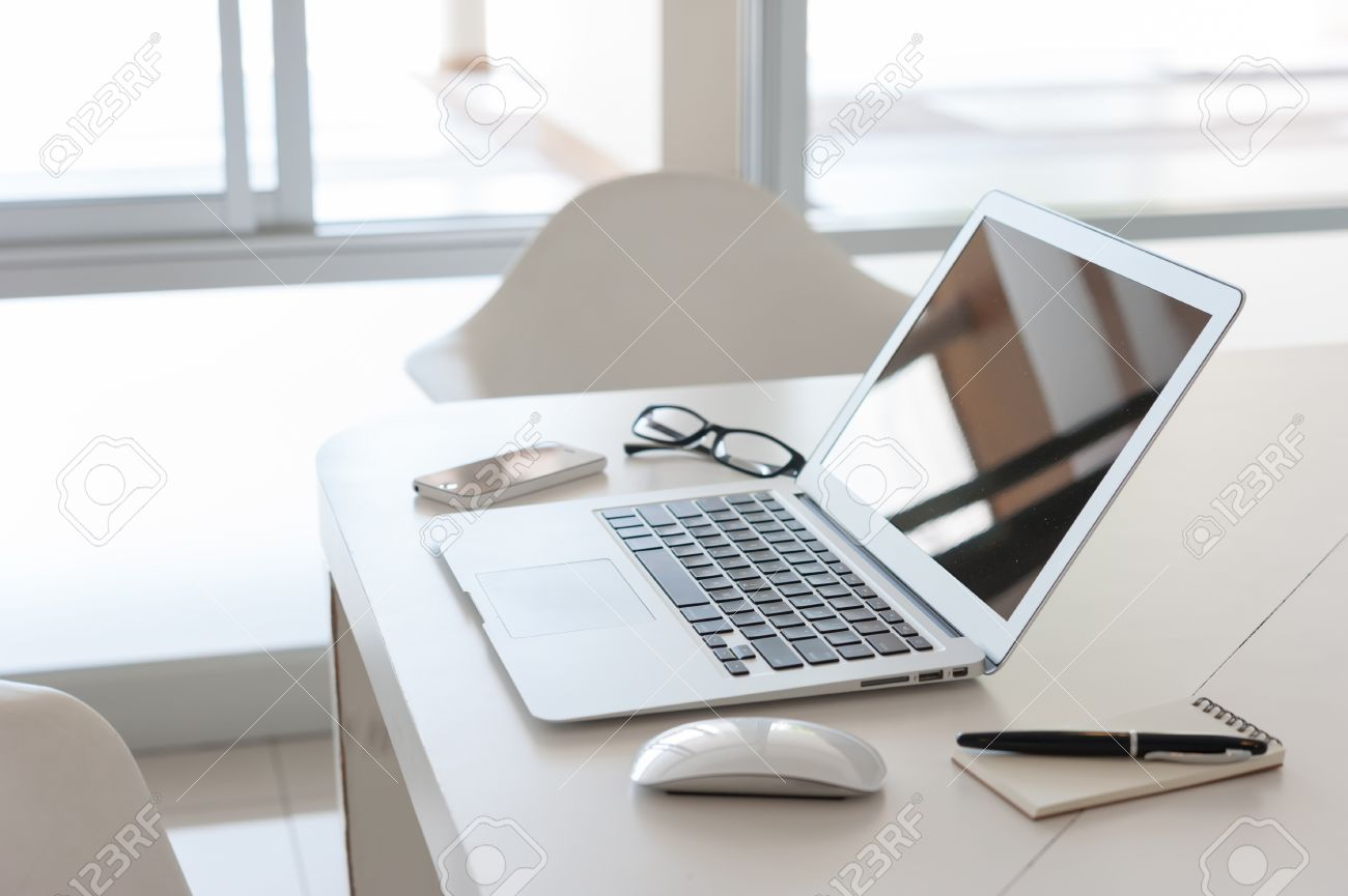 laptop with smartphone and note book on work desk stock photo