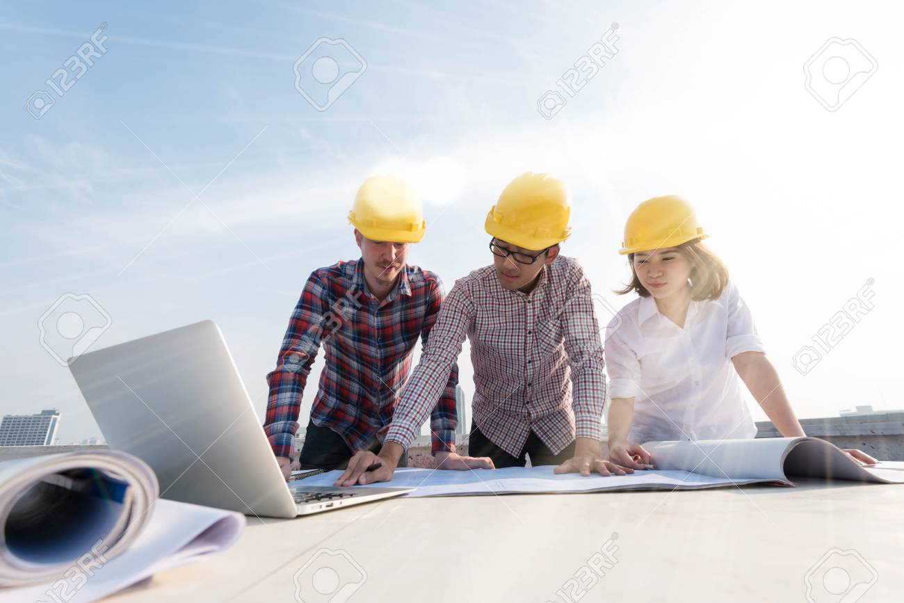 Three construction engineers working outdoors in construction stock photo three construction engineers working outdoors in construction site with blueprint on table malvernweather Images