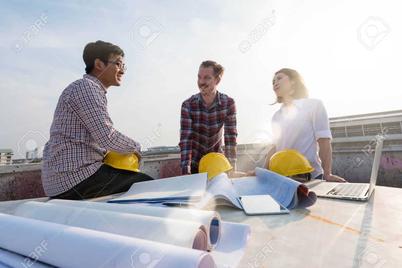 Three construction engineers finished working outdoors in stock photo three construction engineers finished working outdoors in construction site with blueprint on table malvernweather Images