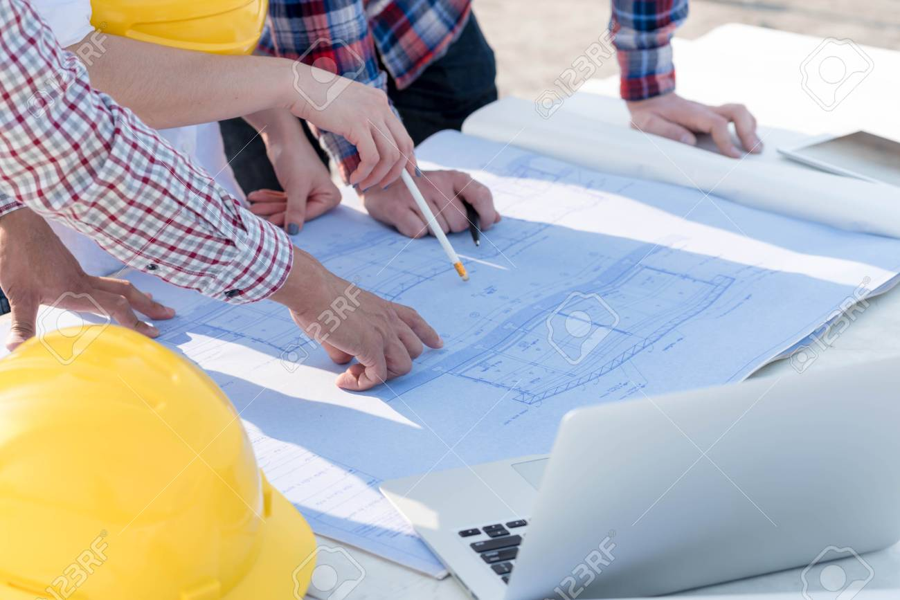 Three construction engineers working outdoors in construction three construction engineers working outdoors in construction site with blueprint on table stock photo 70792926 malvernweather Images