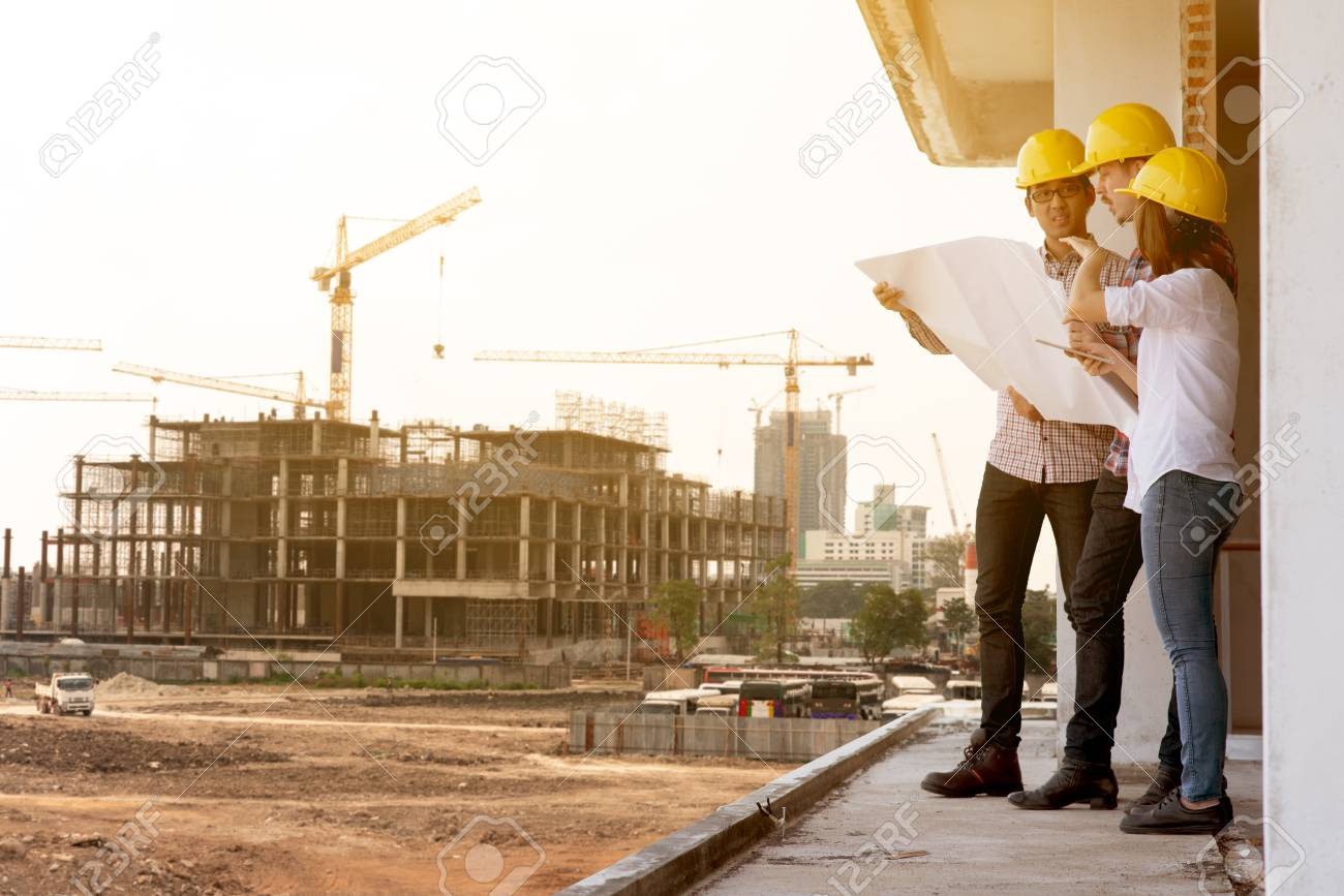 three construction engineers working together in construction site planning for the renovation - 107592751