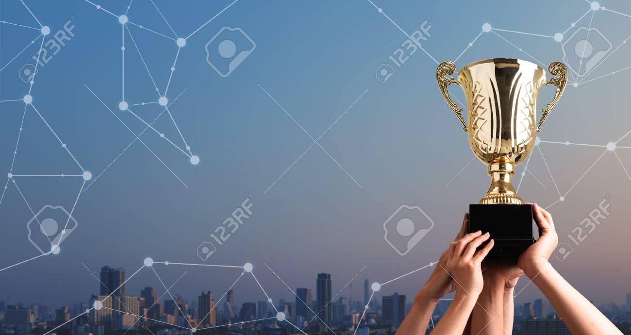 Winning team raise trophy cup with digital background, digital achievement conceptual - 121620951