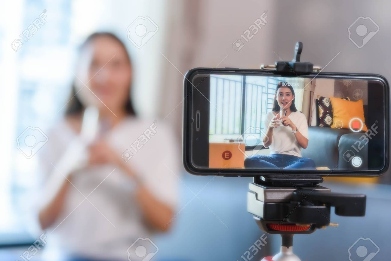 Beauty blogger demonstrating how to make up and review products on live broadcast use smartphone, life of an influencer - 126727559