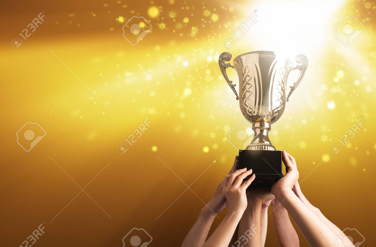Winning team raise trophy cup with background of sky of light ray - 125655863
