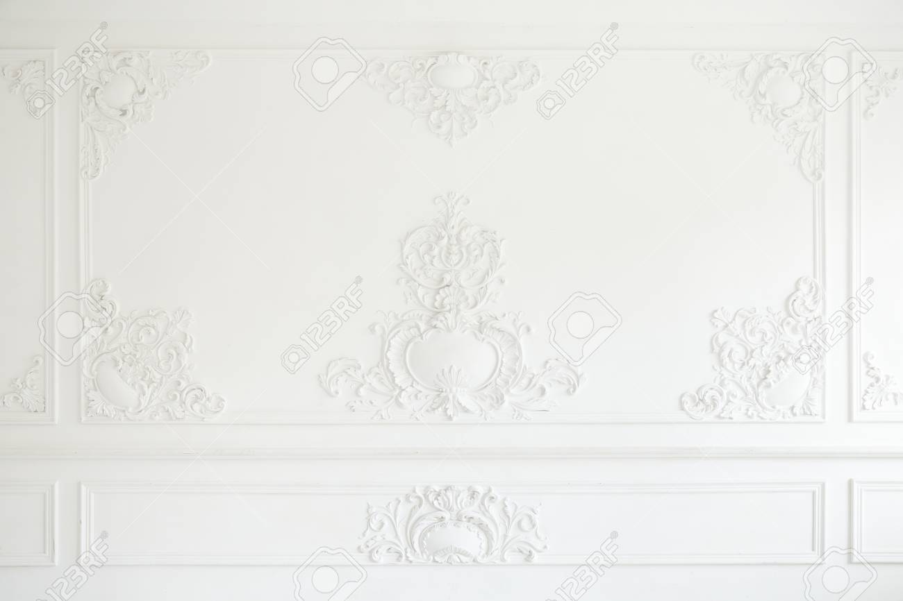 Beautiful ornate white decorative plaster mouldings in studio. The white wall is decorated with exquisite elements of plaster stucco. - 116574924