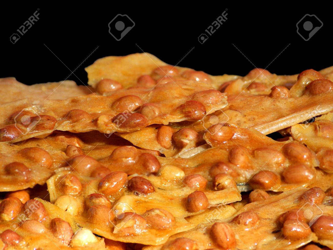 Close view of peanut brittle against black background. Stock Photo - 8605030