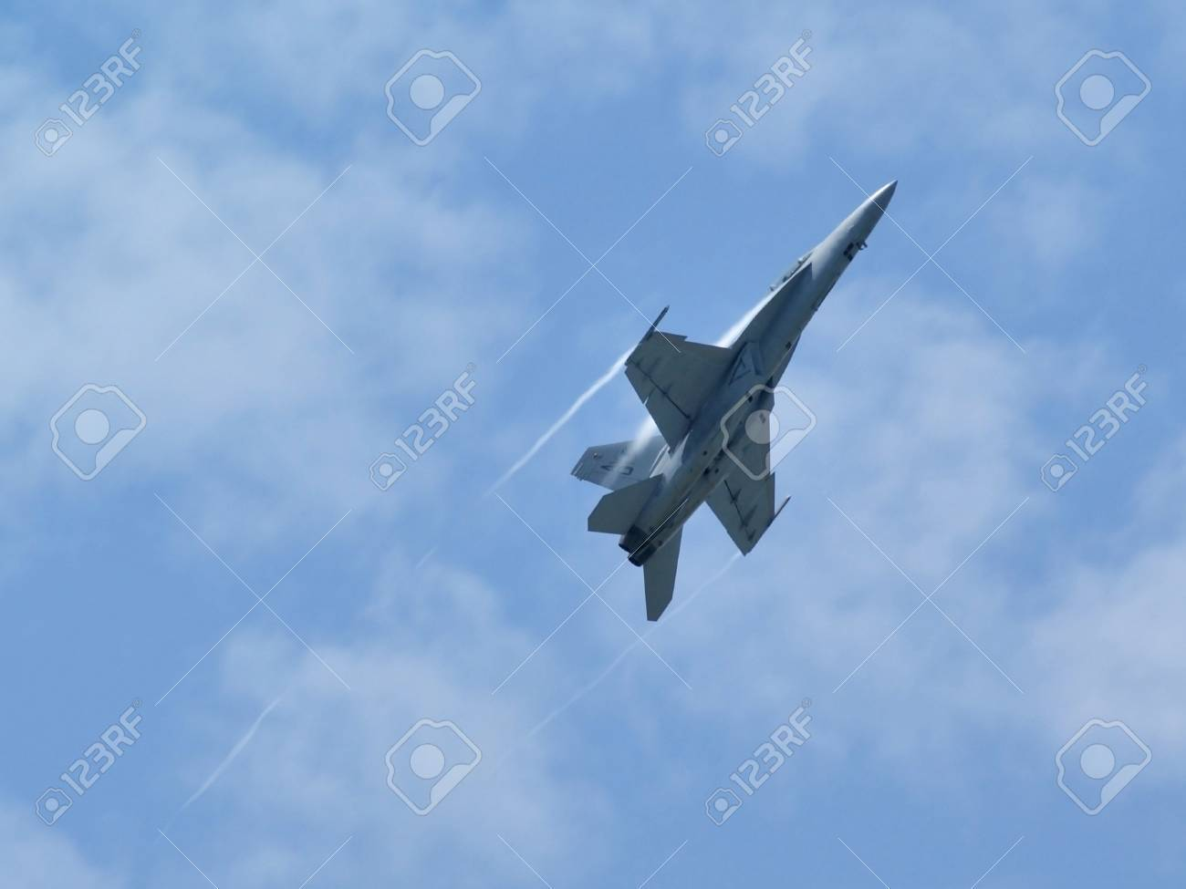 View of a jet fighter climbing with trails visible. Stock Photo - 8669518