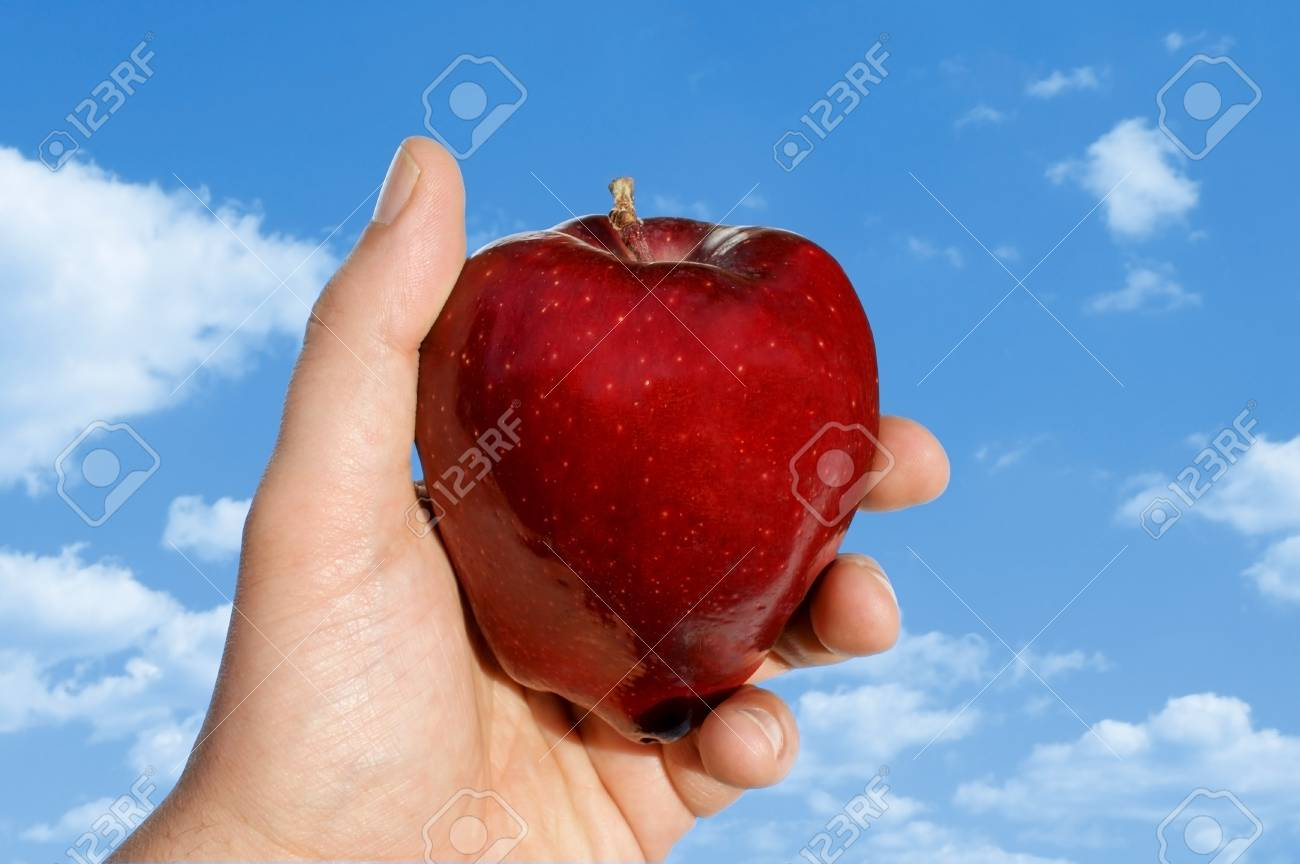 View of an apple in hand against clouds. Stock Photo - 8952161