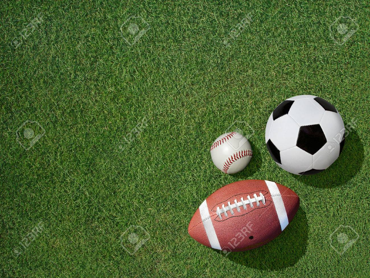 View  of sports equipment including baseball, soccer and football on grass background. Stock Photo - 44539865