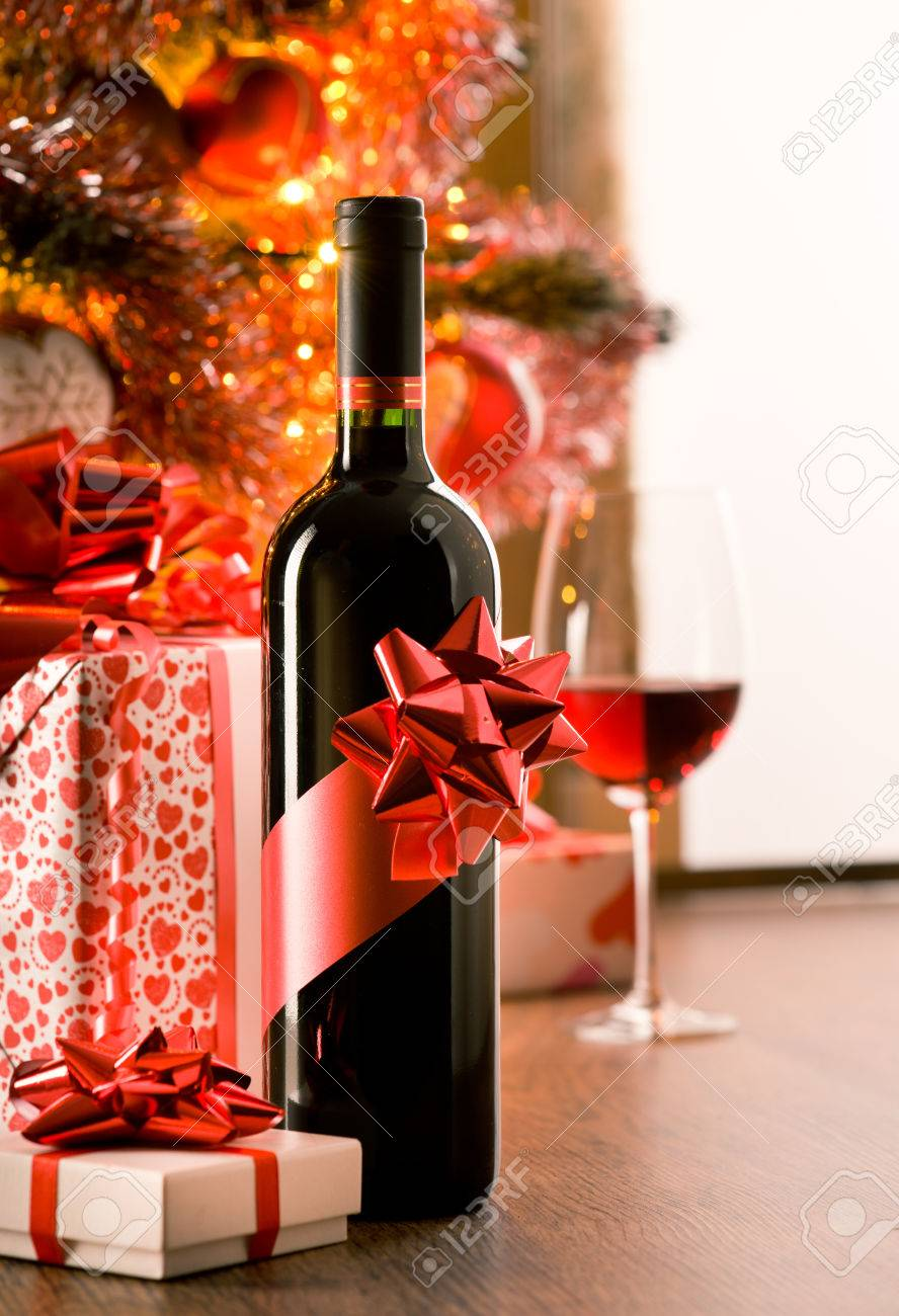 Wine Bottle With Red Ribbon With Christmas Gift Boxes And Tree ...