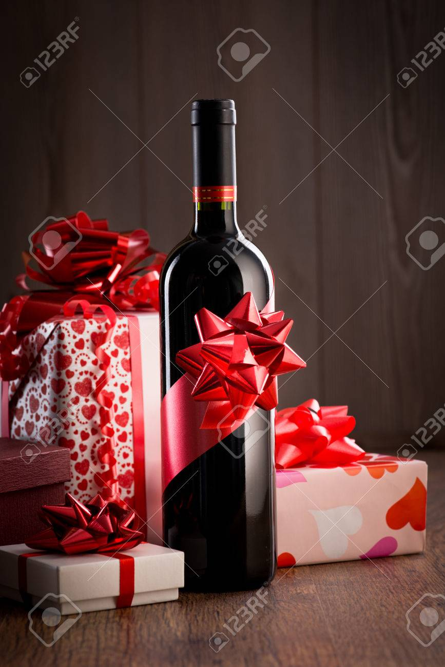 Wine Bottle Gift With Red Ribbon And Colorful Christmas Gift.. Stock ...